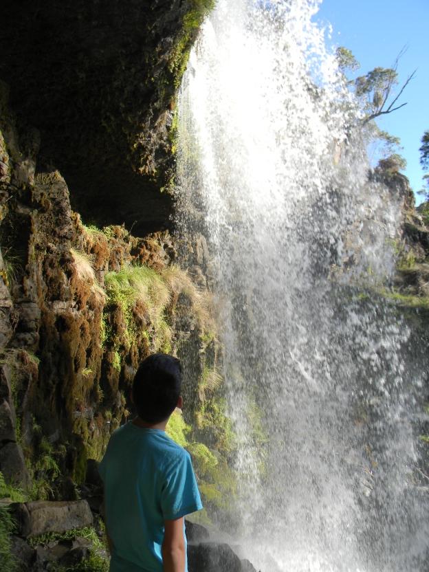 Daniel behind a waterfall